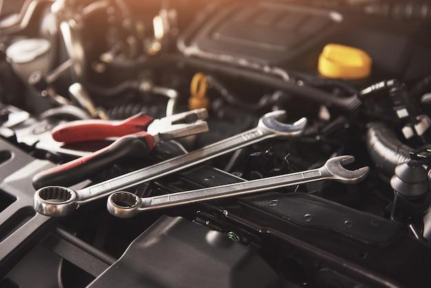 Mano de mecánico revisando y arreglando un automóvil roto en el garaje de servicio de automóviles.