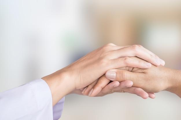 Mano de médico femenino consolando a paciente con desenfoque de fondo de la habitación del hospital