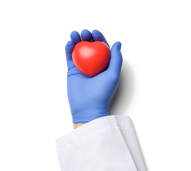 Mano del médico masculino en guantes de látex azul y bata blanca con un corazón rojo, concepto de donación, superficie blanca