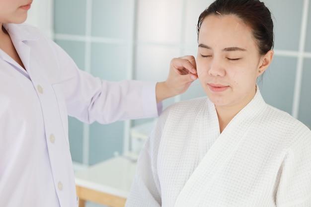 Mano del médico que realiza la terapia de acupuntura. mujer asiática sometida a tratamiento de acupuntura con una línea de agujas finas insertadas en la piel de su cara en un hospital clínico