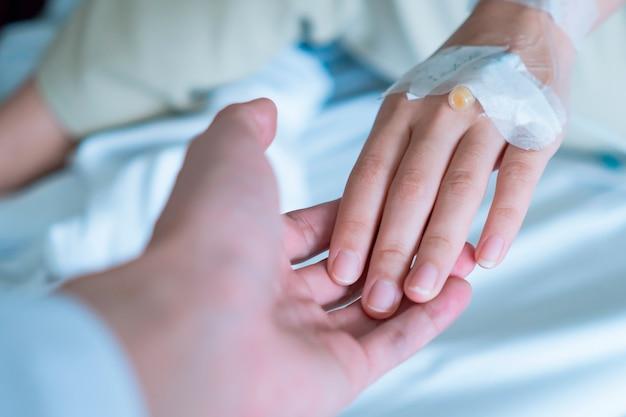 Mano del médico senior tranquilizando la mano del paciente, atención médica médica