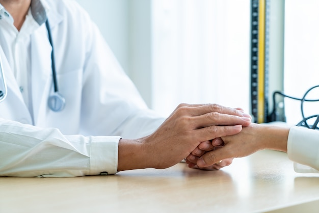 Mano del médico tranquilizar a su paciente femenino