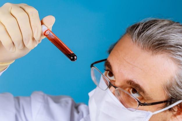 Mano del médico con tubos de ensayo de sangre en el científico en el laboratorio de investigación
