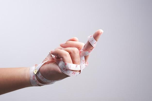 De la mano con la mierda, gesto envuelto por cinta métrica
