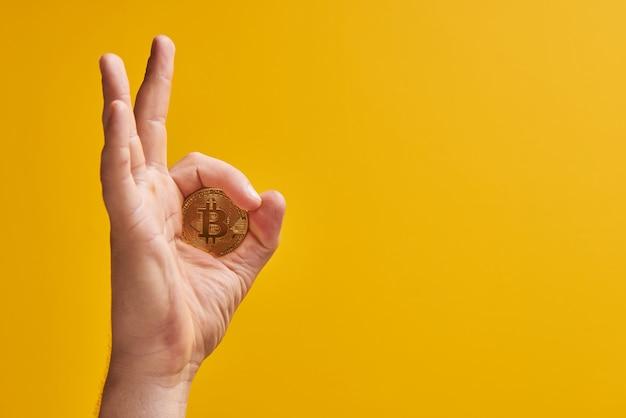 Mano con moneda física bitcoin sobre fondo amarillo, gesto