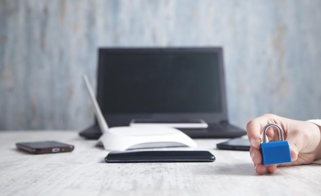 Mano mostrando candado. teléfonos inteligentes, enrutador de internet, computadora portátil en el escritorio. seguridad