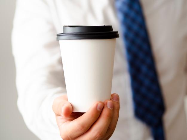 Mano mostrando maqueta de taza de café