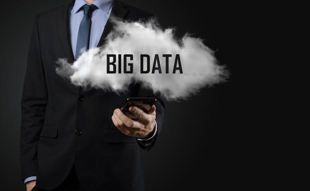 Mano mostrando una nube con las palabras big data sobre superficie oscura