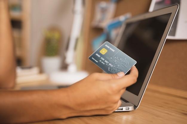 Mano mostrando una tarjeta de crédito junto a una computadora portátil