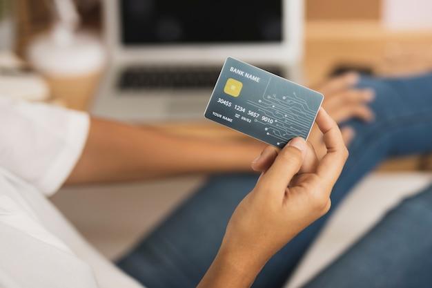 Mano mostrando una tarjeta de crédito simulacro