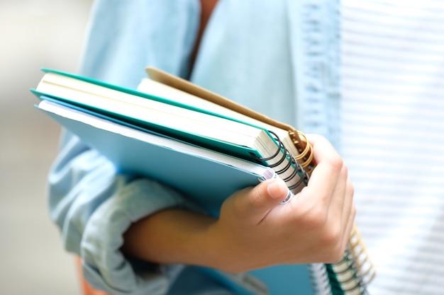 La mano de la muchacha del estudiante que sostiene los libros y lleva el bolso de escuela mientras que camina en el fondo de la escuela, e