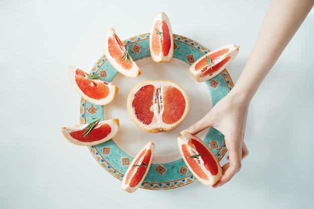 La mano de la muchacha que toma la rebanada de pomelo de la placa blanca. desde arriba. dieta saludable nutrición.