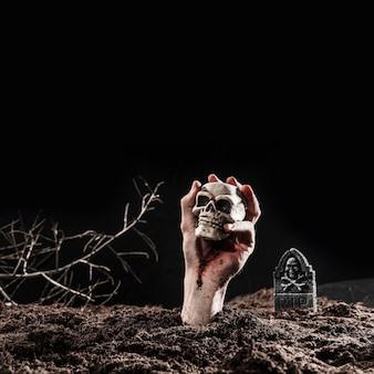 Mano de muertos vivientes sosteniendo el cráneo en el oscuro cementerio en la noche de halloween