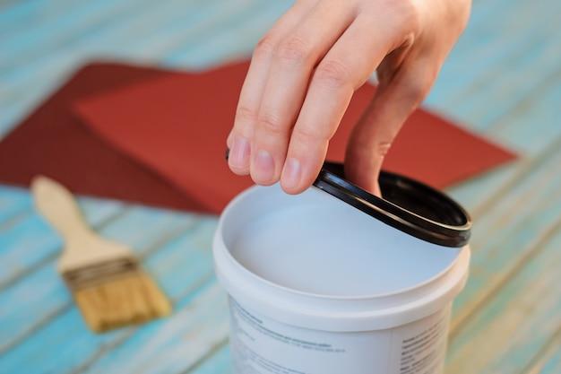 Mano de mujer abierta lata de pintura blanca y tablas de madera preparándose para pintar.