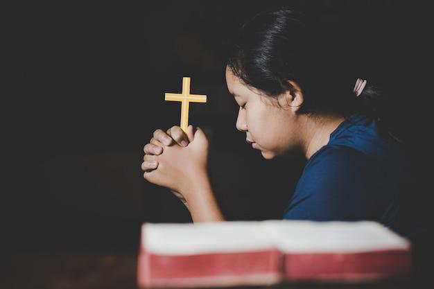 Mano de mujer adolescente con cruz y biblia orando, manos dobladas en oración