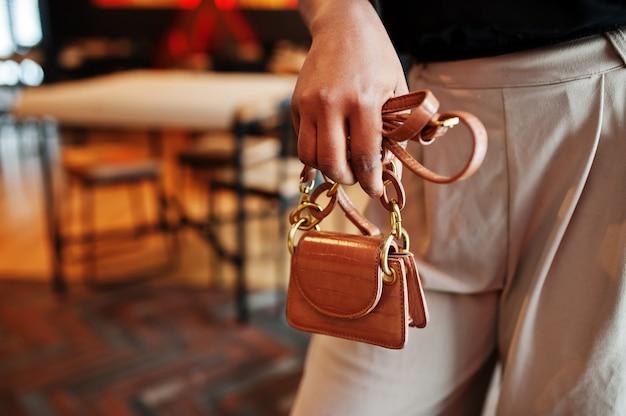 Mano de mujer africana sostenga el pequeño bolso.