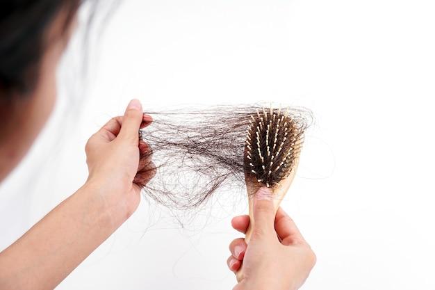 La mano de una mujer agarra el cabello que falta en el cepillo aislado sobre fondo blanco cabello que ha caído