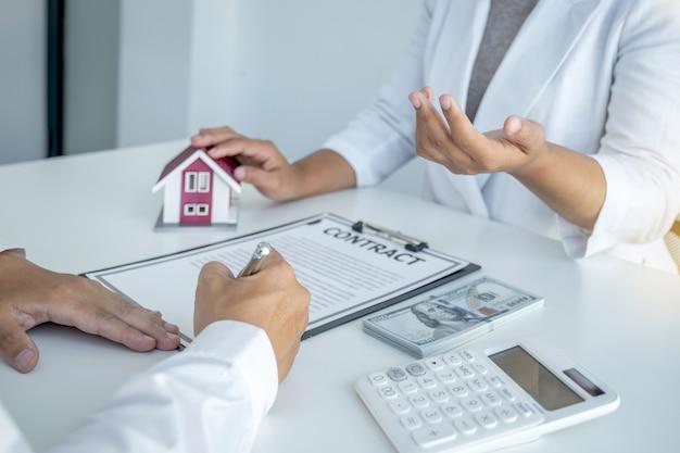 Mano de mujer. el agente de bienes raíces explica el contrato comercial, el alquiler, la compra, la hipoteca, un préstamo o el seguro del hogar a la mujer compradora.