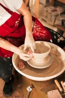 Mano de mujer alisando el tazón con herramienta plana en la rueda de alfarero