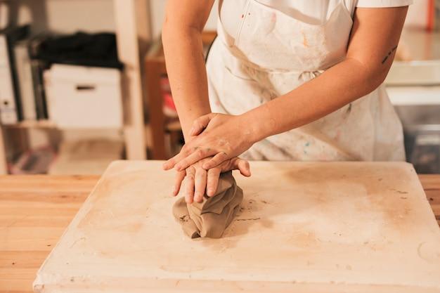 Mano de mujer amasando una arcilla sobre la mesa.