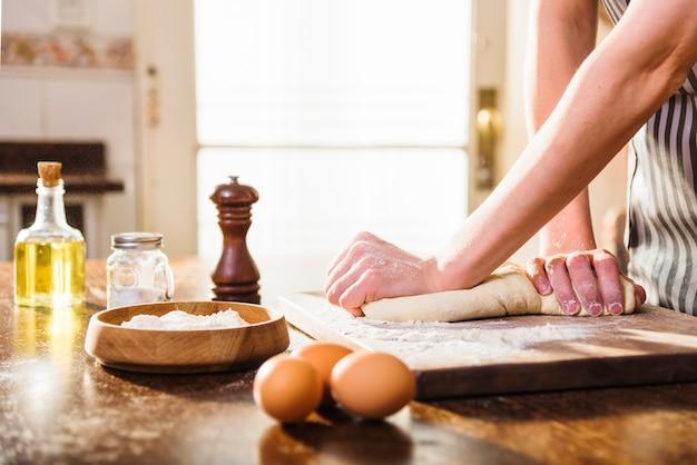 Mano de mujer amasando masa con ingredientes en mesa de madera