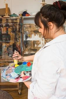 Mano de mujer apretando tubo de pintura amarilla en la paleta de pintura desordenado