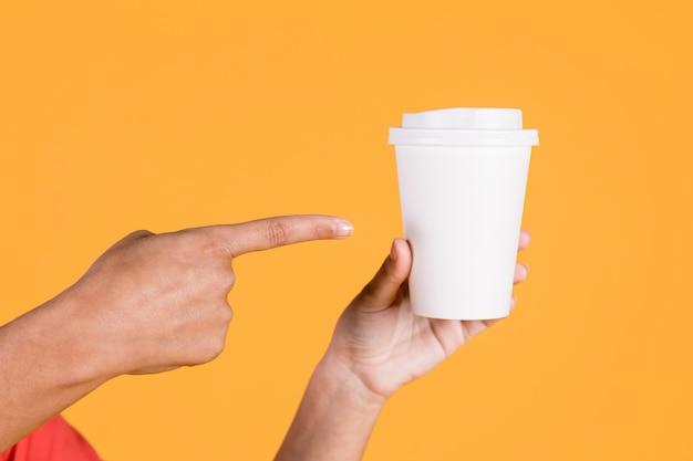 Mano de mujer apuntando sobre vaso desechable en superficie coloreada