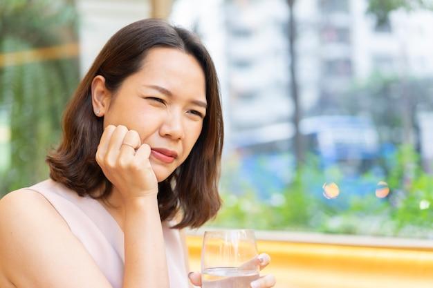 Mano de mujer asiática para masajear mejilla causa de dolor de muelas después de beber agua fría para el cuidado dental
