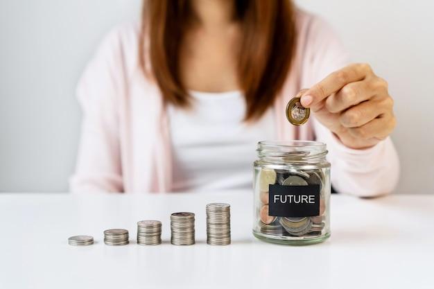 Mano de mujer asiática poniendo monedas en frasco de vidrio sobre fondo blanco de mesa. ahorrar, recolectar dinero para el futuro, concepto de inversión. de cerca