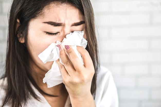 Mano de mujer asiática sosteniendo tejido estornudo de gripe