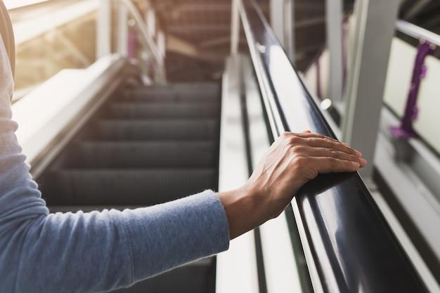 Mano de la mujer en la barandilla de la escalera mecánica en la estación de tren