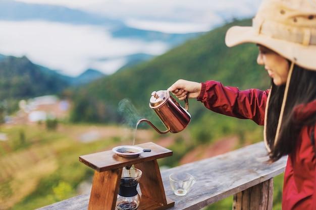 Mano de mujer barista vertiendo agua caliente de jarra para café arábica en filtro en la cima de la montaña