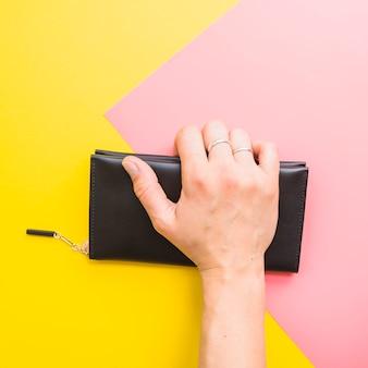 Mano de mujer con bolso clutch