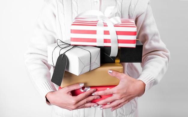 Mano de mujer con caja de regalo y etiqueta de papel aislado en blanco