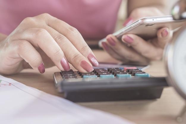 Mano de mujer calculando con calculadora y teléfono inteligente