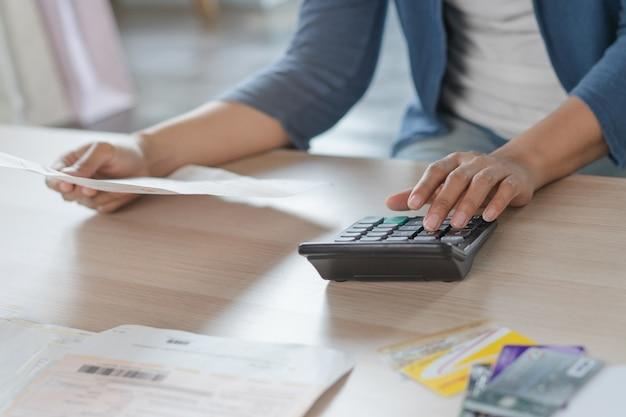 Mano de mujer calculando gastos mensuales y deuda de tarjeta de crédito.