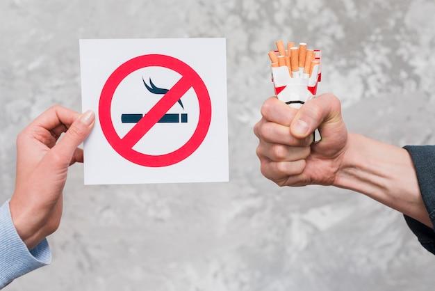 Mano de mujer con cartel de no fumar cerca de la mano del hombre con paquete de cigarrillos