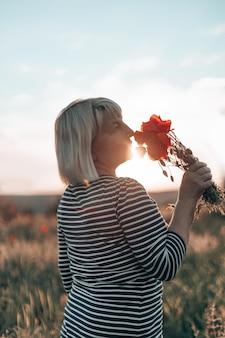 Mano de mujer caucásica sosteniendo un ramo de flores de amapola sobre fondo de pradera al atardecer