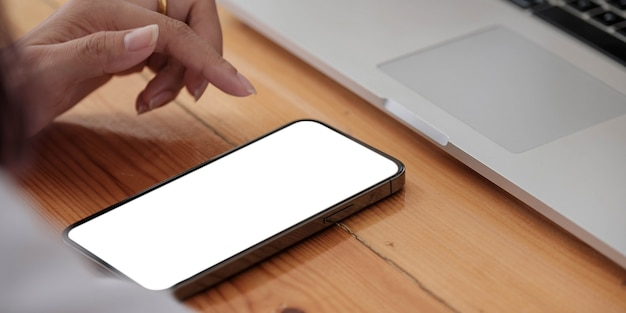 Mano de mujer de cerca con un teléfono inteligente con pantalla en blanco en la cafetería cafetería.