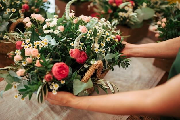Mano de mujer con cesta de flores frescas