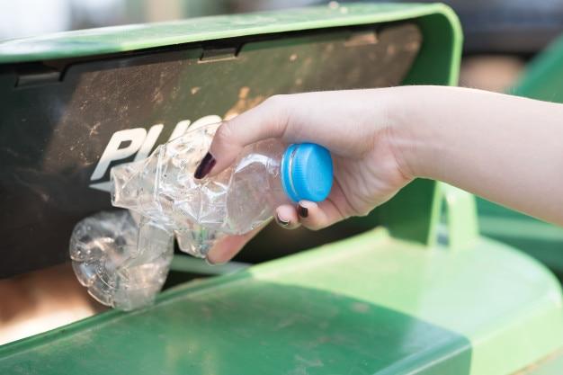 Mano de mujer closeup lanzando botella de plástico vacía en papelera de reciclaje