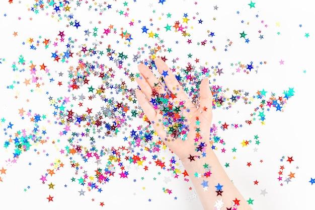 Mano de mujer con confeti estrella color festivo