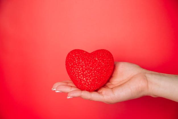 Mano de mujer con corazón decorativo rojo.