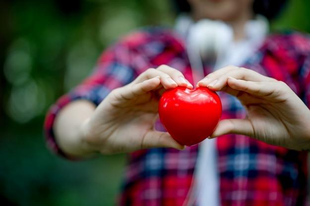 Mano de mujer y corazón rojo.