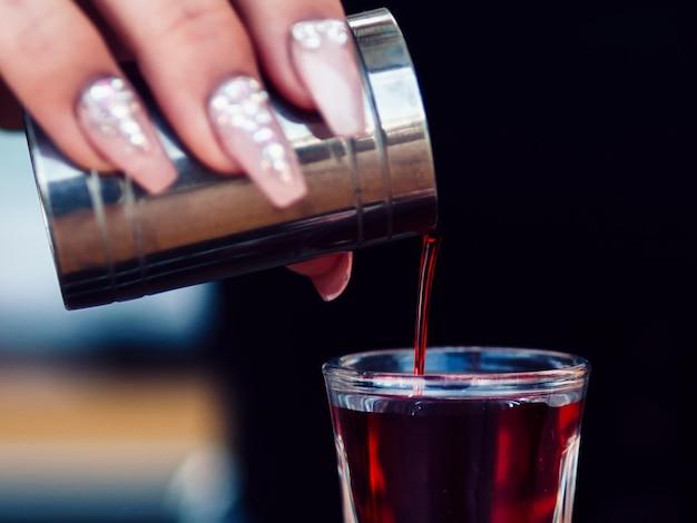 Mano de la mujer de la cosecha que agrega la bebida en tiro