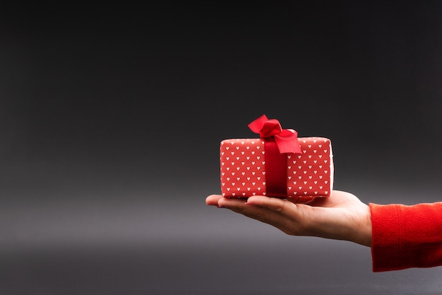 La mano de la mujer da un presente en el fondo negro, concepto del día de boxeo de la navidad