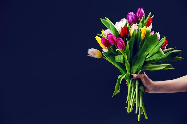 La mano de mujer da un ramo de tulipanes