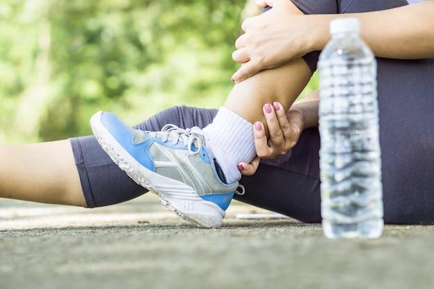 Mano de mujer deporte masajeando su dolor de pierna