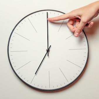 La mano de la mujer detiene el tiempo en un reloj redondo, el dedo femenino toma la flecha de minutos del reloj hacia atrás, la gestión del tiempo y la fecha límite