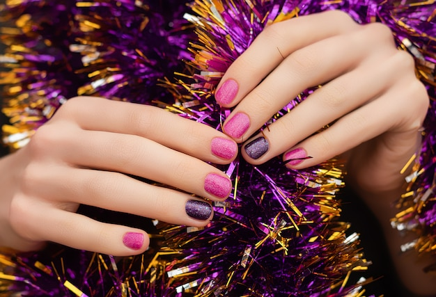 Mano de mujer con diseño de uñas de navidad y año nuevo sostener esfera de juguete brillante